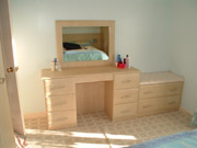 A fitted dressing table and chest of drawers