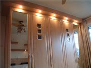 Spotlights on a fitted wardrobe with mirrored door panels